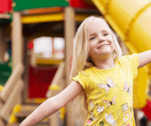 Child with arms out wide looking happy, playground equipment in the background