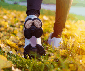 someone walking on grass covered with fallen leaves